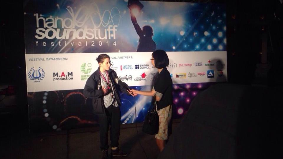 Micachu stands in front of a hanoi sound stuff billboard being interviewed by a reporter