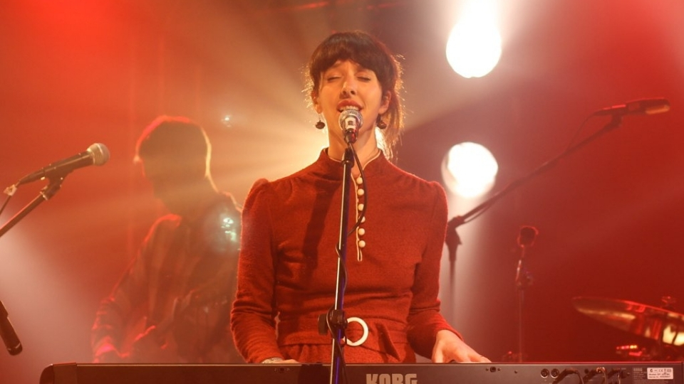 9bach's Lisa Jên Brown singing on stage behind a Korg keyboard
