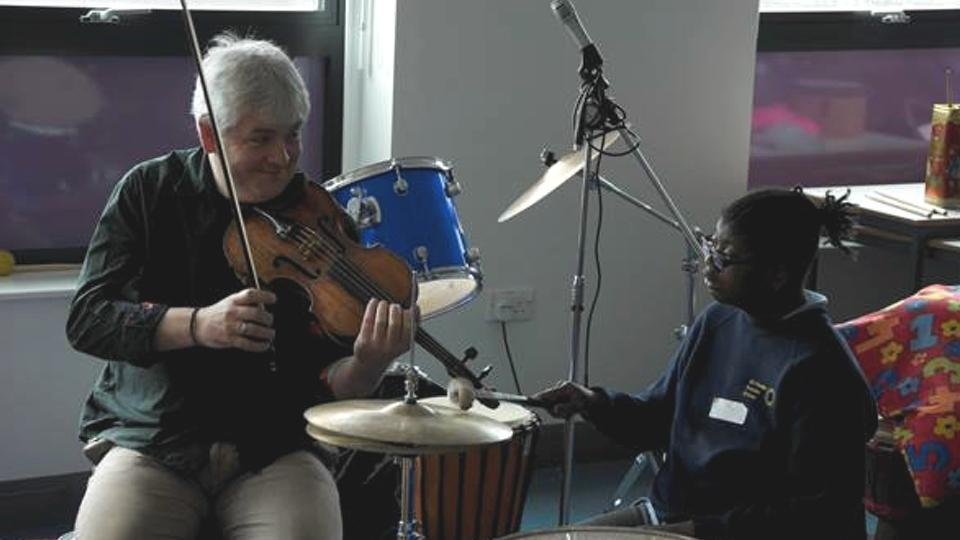 A musician holds a violin as a child plays percussion