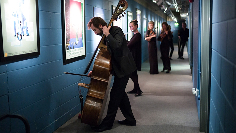 Aurora Orchestra players backstage, musician standing at the forefront with double-bass in focus