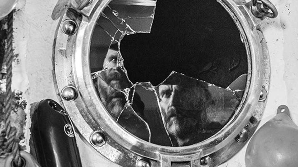 Man's reflection shattered in broken porthole - a still from BAIT film