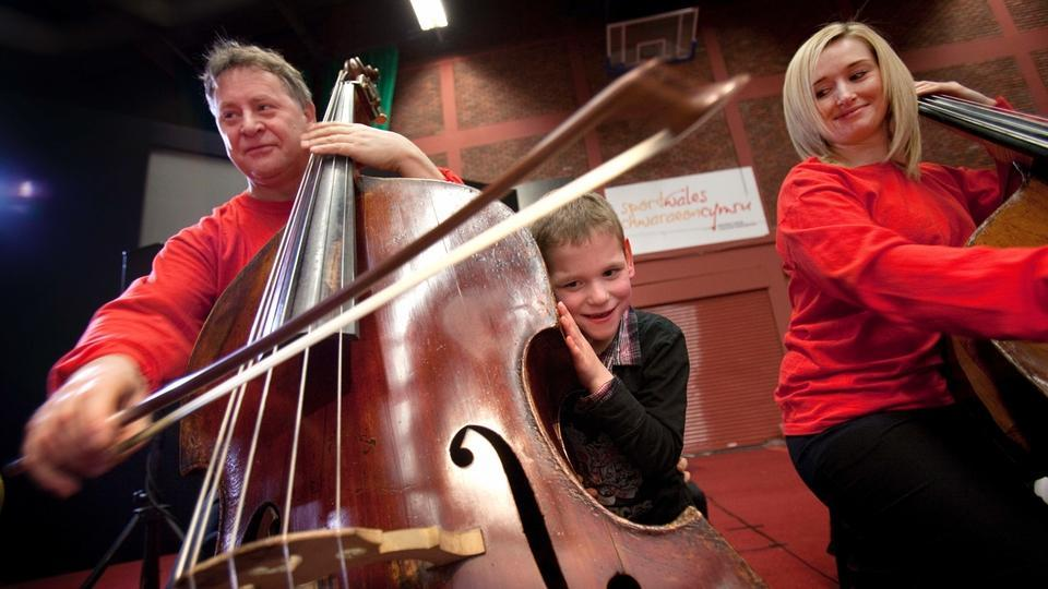A child presses his ear against a double bass as a musician plays