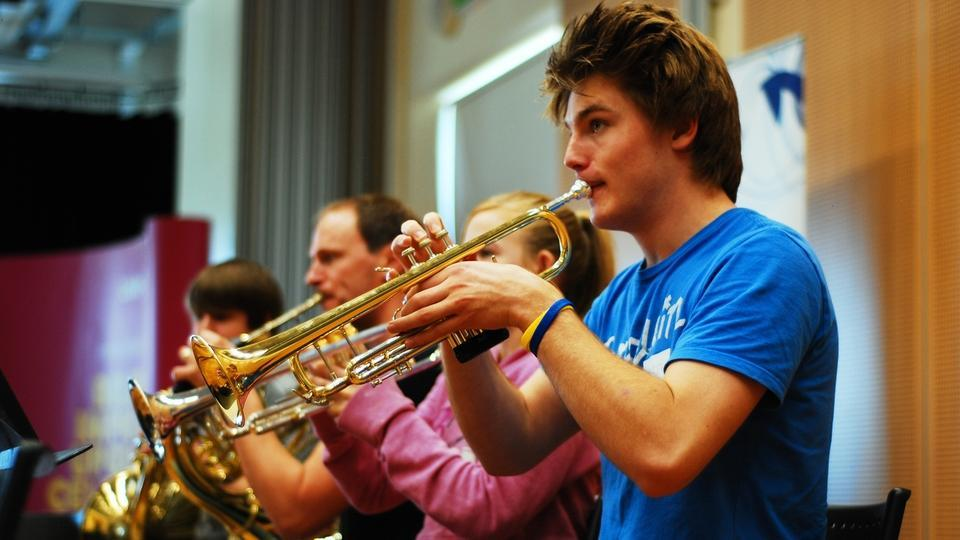 Four musicians play trumpets in rehearsals