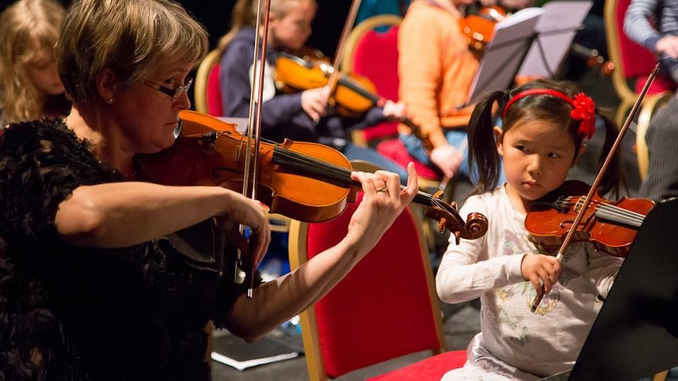 A young girl is playing a violin as she watches an older woman play