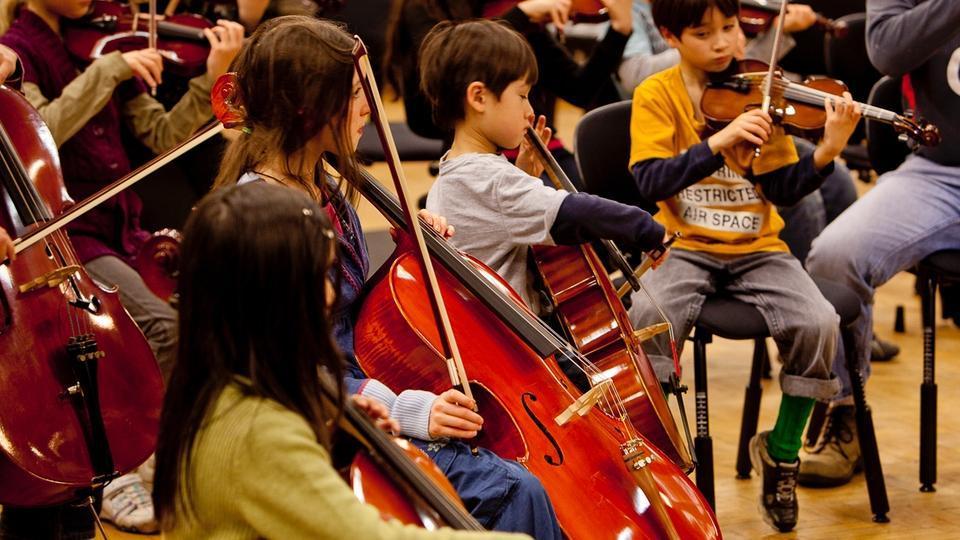 Young children play various string instruments