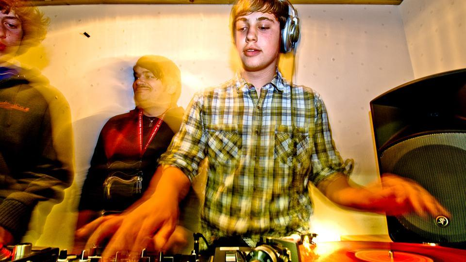 A young DJ mixes on vinyl decks