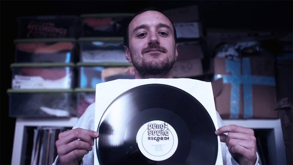 Bearded man holds up a vinyl record