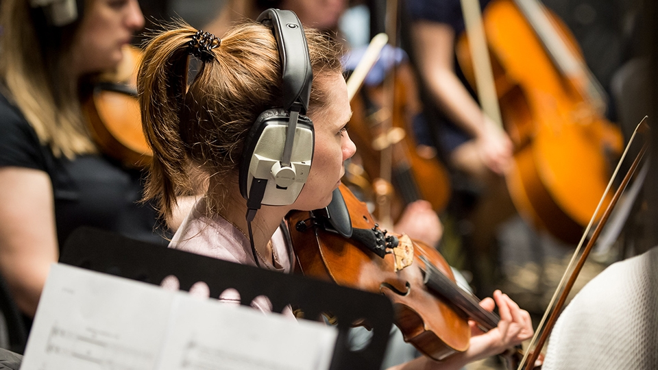 Violinist wearing headphones waits for cue