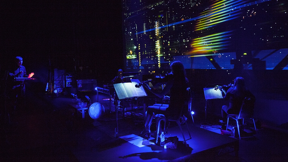 Violinists in front of live projection during performance
