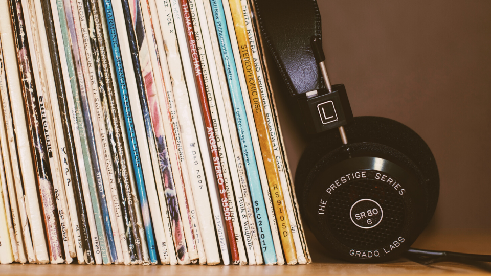 A pair of headphones leaning on a rack of LPs.