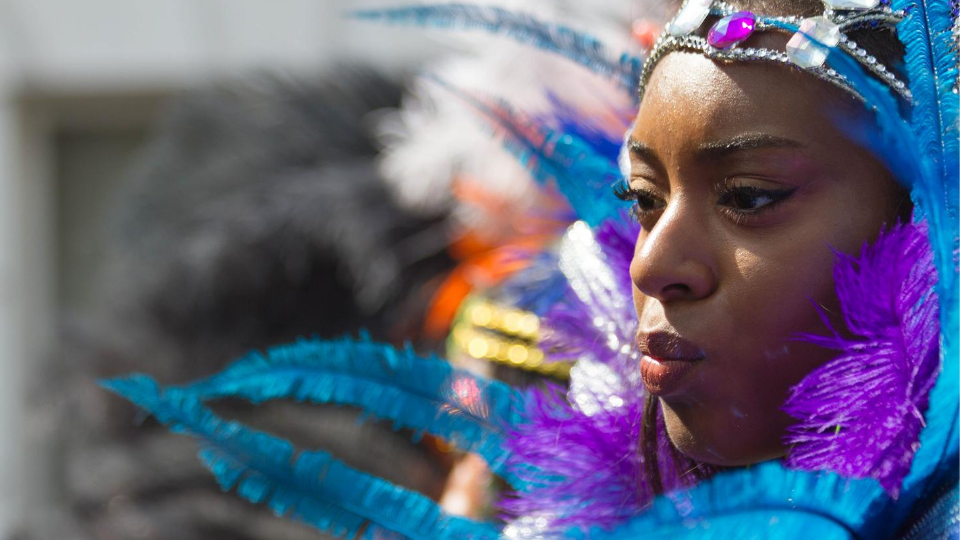 Close-up of dancer's face wearing blue and purple feathered head dress