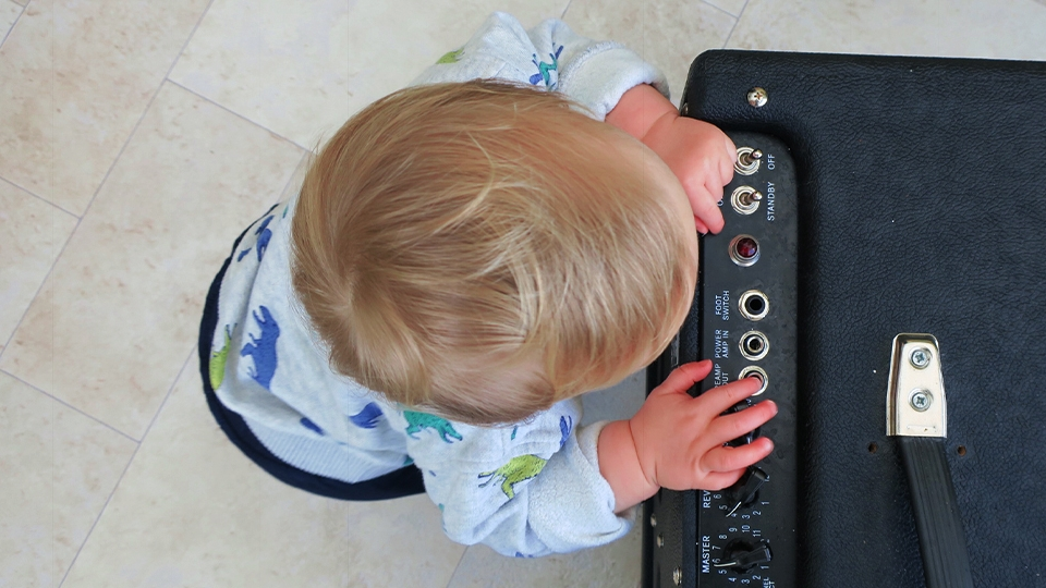 Baby next to guitar amplifier
