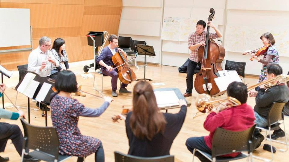 Orchestral musicians perform as a group in a workshop