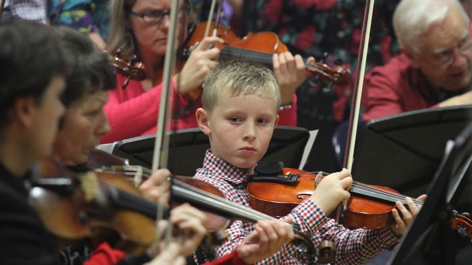 A young boy holds a violin and watches other violinists play